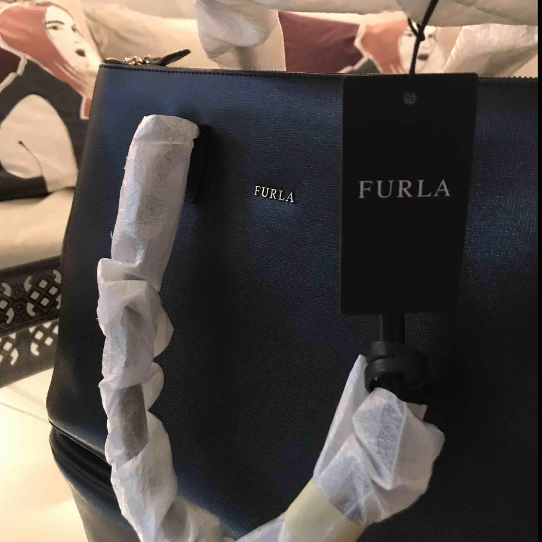 En svart väska ifrån äkta Furla Dust bag och prislapp tillkommer! Kvitto finns ej kvar. Aldrig använd och handtagen är fortfarande inpackade.  Vid flera intressen, budgivning!. Väskor.