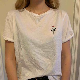 En vit t-shirt med ros tryck på vänster bröst och med rosor och text på baksidan, H&M!