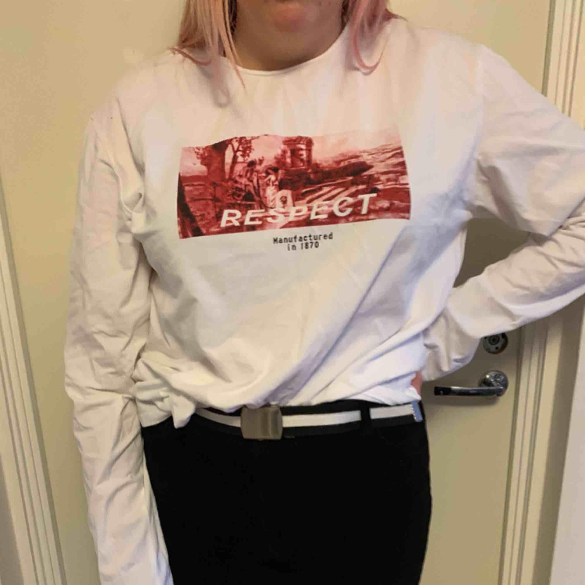 En väldigt stor vit tröja, med tryck på framsidan. Köp på shein där av billigt pris. Frakt tillkommer. Toppar.