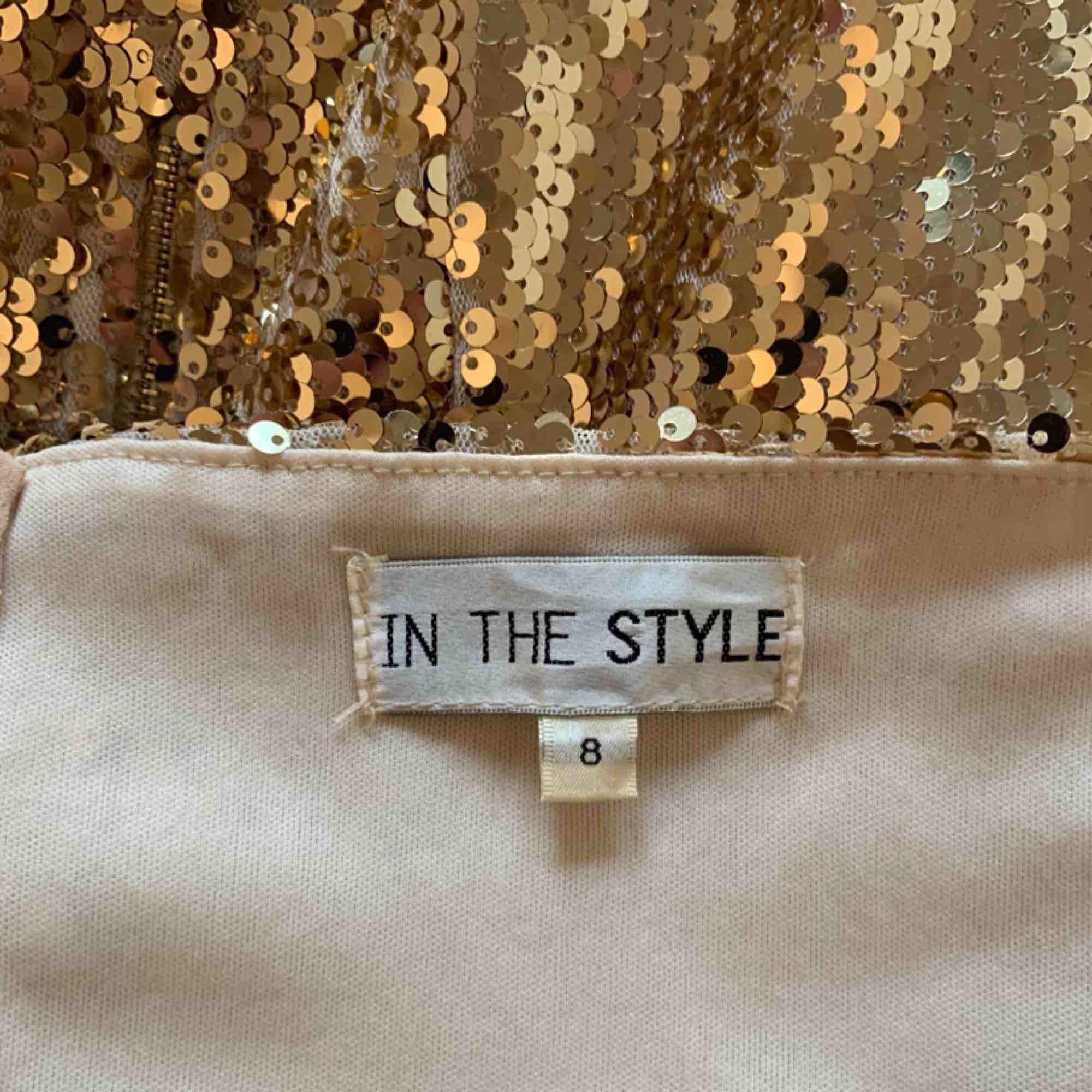Kort guldfärgad tubklänning från In The Style storlek 8 (36) silikon på insidan så den ej glider ner. Fint skick.  Möts upp i Stockholm eller fraktar.  Frakt kostar 59kr extra, postar med videobevis/bildbevis. Jag garanterar en snabb pålitlig affär!✨. Klänningar.