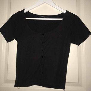en croppad svart tröja med knappar hela vägen ner