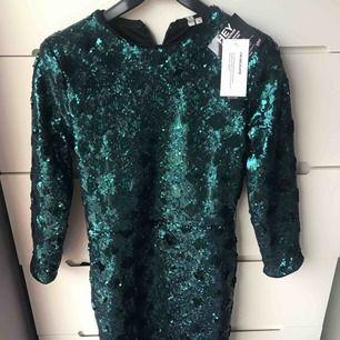 Grön glittrig klänning från Nelly helt ny och oanvänd säljer för att jag inte tycker den sitter bra på mig. Perfekt inför jul och nyår. Skynda fynda!
