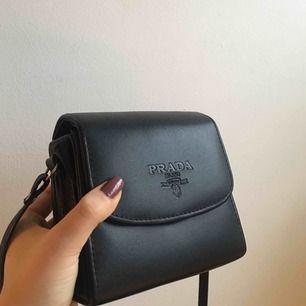 Min bästa Prada väska 😻 vill inte sälja men har alldeles för många 💔 har vart så praktisk när man ska ut! Har lite skavanker på insidan (se bild 2) men annars är den hel och fin. Bandet går att justera