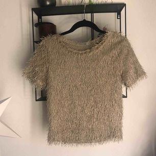 T-shirt med fransar i sandfärgat tyg från Zara. Använd 1 gång. Tröjan är kanska kort kort och går ungefär till naveln. Passar mer som xs. (Frakt tillkommer)