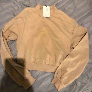 En brun/röd/beige croppad/kort sweatshirt från Bershka. Oanvänd med lapp kvar. Storlek S. 100kr plus porto 63kr så 163kr