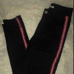 Snygga tighta högmidjade jeans med slitningar på knäna!! Röd, vit och svart revär på sidan❤️🖤sparsamt använda