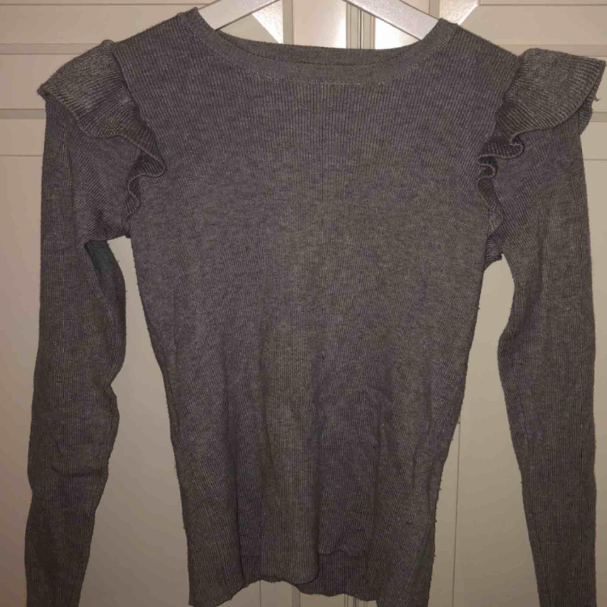 super fin grå ribbad tröja ifrån bikbok med detaljer på axlarna, fint skick då den inte används så ofta. säljer pga att det inte riktigt är min stil längre. Tröjor & Koftor.