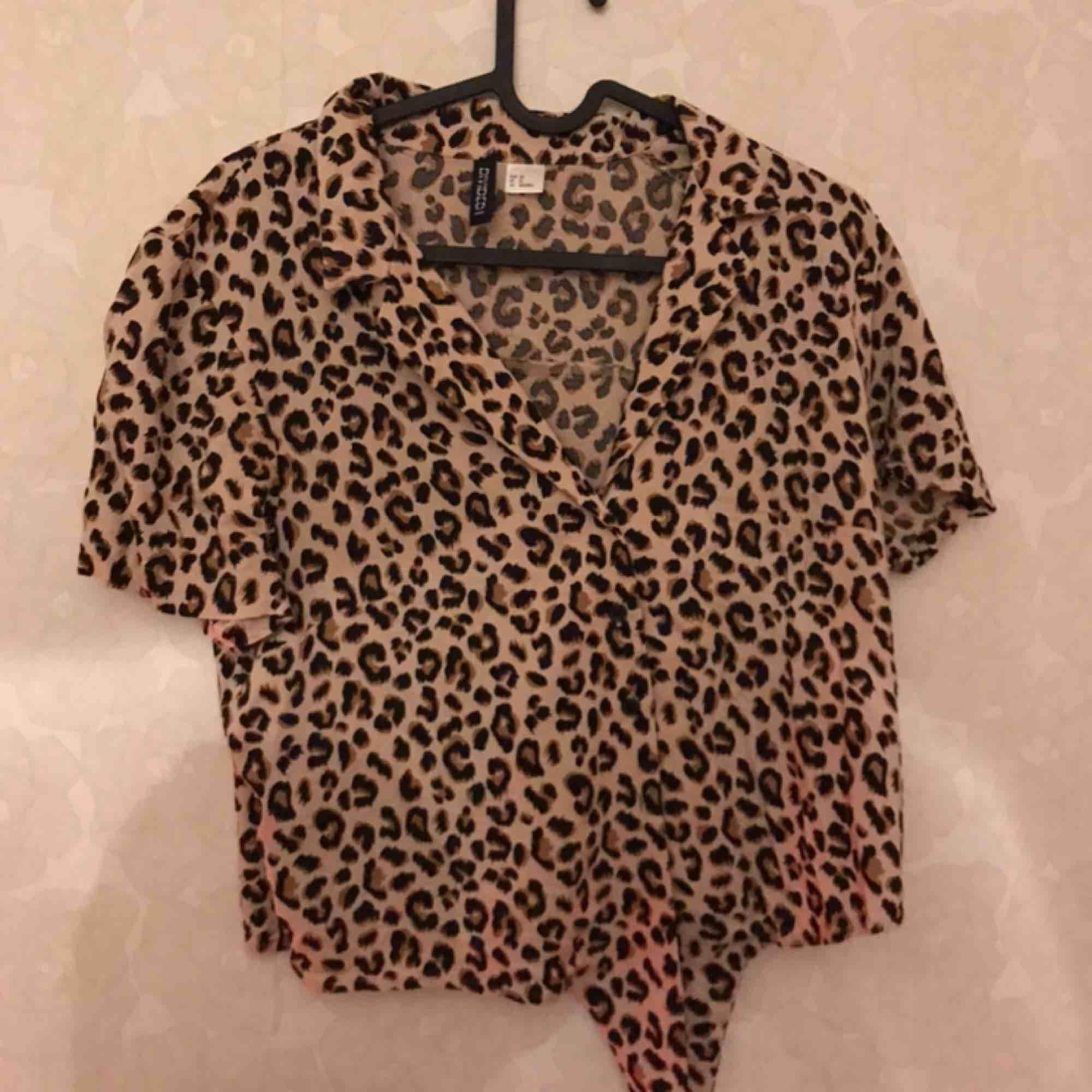 Säljer min snygga leopardmönstrade tröja ifrån H&M i storlek 38. Sluts med knappar och man kan knyta i änden utav tröjan. Använd 1 gång . T-shirts.