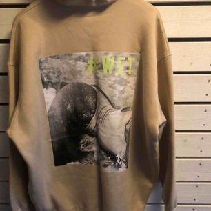 Oversized beige hoodie med stort tryck på ryggen.  Storlek S men som sagt oversize så passar många storlekar