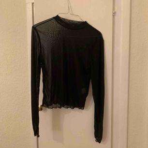 Svart tröja som man ser lite igenom. Fint till under t shirt eller på fest. Frakt tillkommer