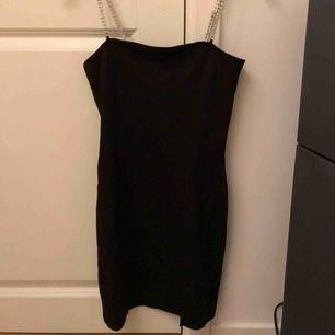 Svart festklänning med silverstenar till axelband.  Kortare klänning med en liten slits.