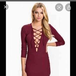 Vinröd klänning med snörning fram. Mjukt material från Nelly stl small. Fint skick.