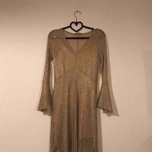 Somrig guld-glittrig klänning med underklänning Skick: Oanvänd, köpt second hand. Fraktkostnad tillkommer