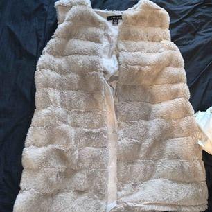 Fuskpäls väst från mnewyorker, inget fel på den. Den är fin och varm och kan knäppas samt att bälte tillkommer. Fraktar då tillkommer frakt.