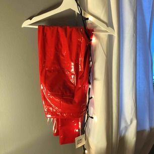 Röda lackbyxor med fickor och dragkedja från ASOS. Aldrig använd och ( prislappen är kvar!! )  Köparen står för frakten!!