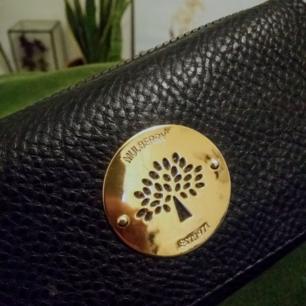 Svart plånbok med gulddetaljer. Plats för många kort. Inköpt för två år sen. Finns i Stockholm, kan skickas.
