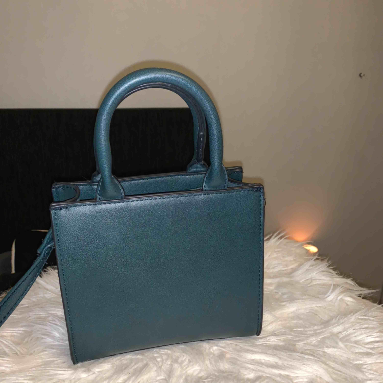 Väska från Bershka i en väldigt fin grön färg, axelband medföljer.. Väskor.