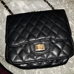 En superfin svart väska med guld detaljer, säljer pga ingen användning för den. Väldigt praktisk väska som är lätt att ha med sig.