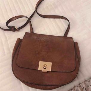 Brun väska med svarta sömmar, och guldiga detaljer! Den är även justerbar, och går att göra längre/kortare!:)  Kan hämtas i Varberg, annars står köparen för frakten!:)