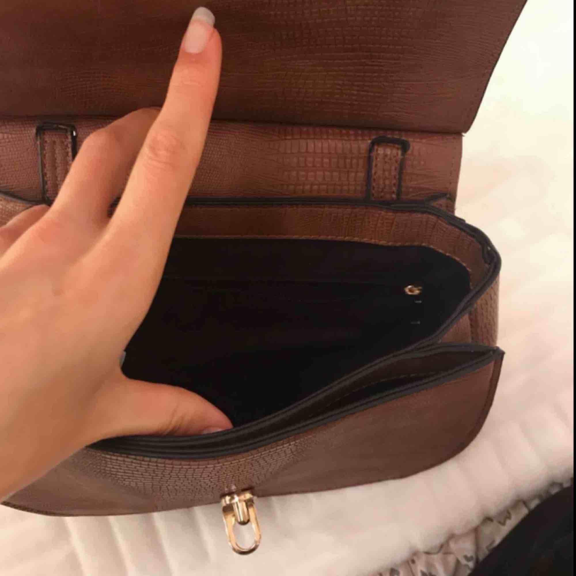 Brun väska med svarta sömmar, och guldiga detaljer! Den är även justerbar, och går att göra längre/kortare!:)  Kan hämtas i Varberg, annars står köparen för frakten!:). Väskor.