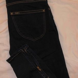 Säljer mina helt oanvända mörkblå Lee jeans. Storleken i midjan är 24 och längden är 29, motsvarar  ungefär en xs. Jeansen är mitt/lågmidjade och har en snygg dragkedja längst ner på båda benen.