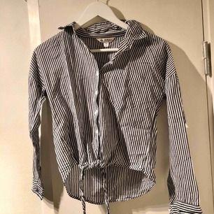 Kort skjorta som knyts längst ner. Sparsamt använd. Ärmarna går att vika upp och knäppa fast!