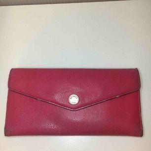 En rosa plånbok som får plats mycket i