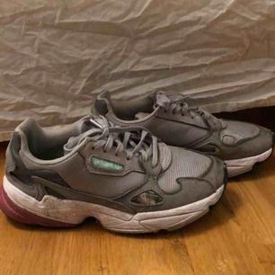INTRESSEKOLL  Adidas sneakers köpta i somras. Gråa med lite färg här o där. Lite slitna på innersidorna.