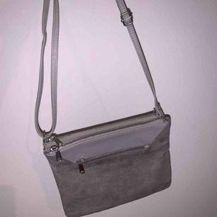 Helt oanvänd väska med tre olika fack. Väskan är i två material och har justerbart axelband.
