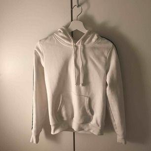 En snygg vit hoodie med svarta sträck på ärmarna, använd endast en gång.