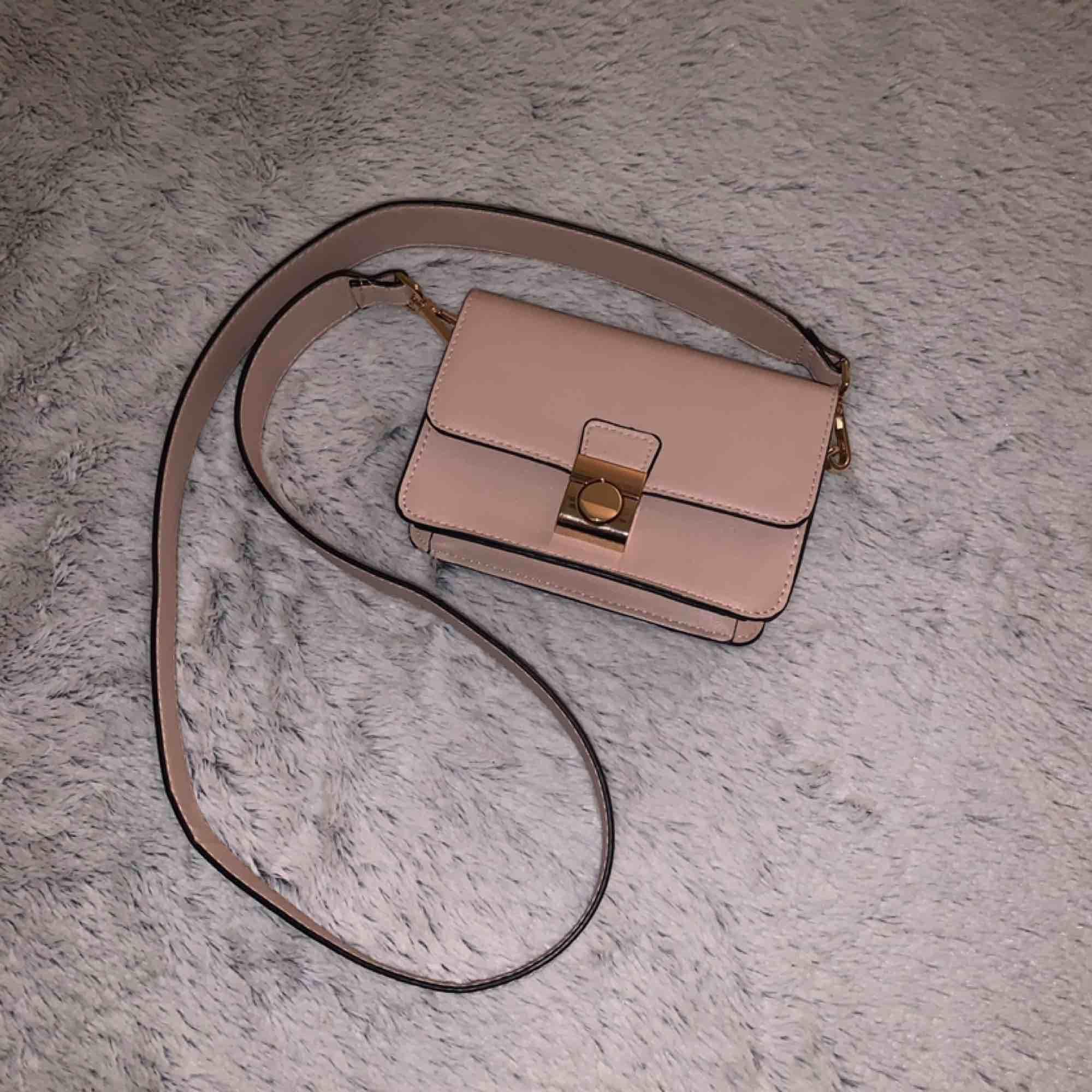 Varför inte köpa en liten rosa beige handväska till nästa festlighet eller som present kanske? Använd bara en gång. Inga skador som helst. Frakt tillkommer. Väskor.