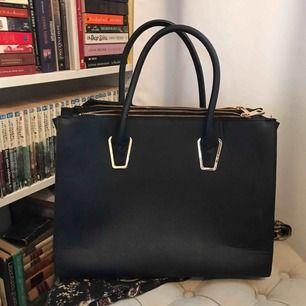 Smidig svart väska med tre stora fack och två små! Perfekt om man går i skolan eller har med sig datorn lite då och då!