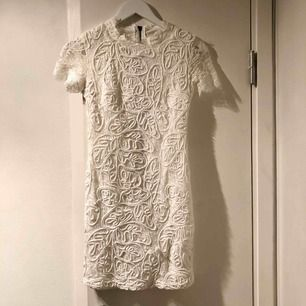 Vit klänning i spets, endast använd en gång! Tajt modell, knäpps i ryggen. Köpare står för frakt :)