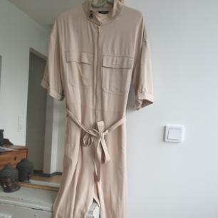 Snygg beige jumpsuit byxdress från Lindex. aldrig använd! bara provat. storlek s men sitter oversized. fickor på framsidan och baksidan. Med knytband. Kan skickas annars finns i Malmö!