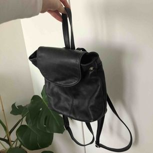 En svart liten väska med ytterfack och innerfack, i fint skick.  Spännbara band.