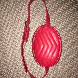 Snygg röd midjeväska använd några gånger i sommar men är i bra skick. Den ser ljusröd ut på de två första bilderna men är som på den sista!<3