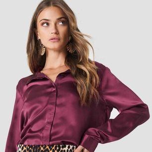 Vinröd satin skjorta från Ruth&circle. Ett par trådar har lossnat (sista bilden) där fram i höjd med nedersta knappen, därav priset. (Frakt tillkommer)