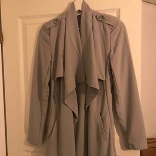 Ljusgrå trench coat från Nelly, köpt för ca 2 år sedan. Aldrig använd! Köparen står för frakten!