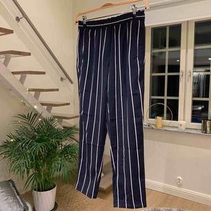 Marinblå- och vitrandiga kostymbyxor med resår i midjan. Perfekta för en sommarkväll där det är för varmt för jeans men för kallt för shorts. Är i fint skick. Hör av dig privat vid intresse!