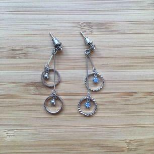 Silvriga dinglande örhängen med två små blåa stenar. Aldrig använda. Frakt 9kr tillkommer. Rengör innan jag skickar.