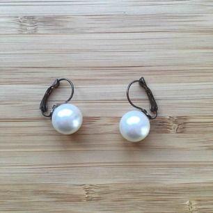 Vita pärlmformade örhängen, knäppet är bronsfärgst och lite slitet. Frakt 9kr tillkommer. Rengör innan jag skickar.