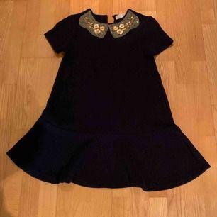 Jag säljer min jättefina blåa klänning med gulddetaljer och blommor på kragen. Det är ett väldigt tjockt och varmt material.   Kan skicka fler bilder och mer info om det skulle behövas.  OBS köparen står för frakt!