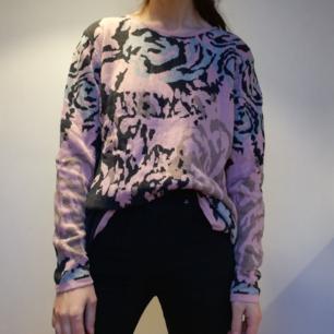 Rosa stickad tröja med camoflauge-mönster gjord i ullblandning. Knappar längs baksidan som även går att vända så man har det fram. Stl L men sitter oversize på mig som har stl XS. Väl använd och lite nopprig om man kollar nära. Frakt 63 kr.