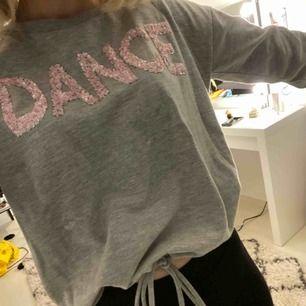 grå tröja från Springfield med DANCE i rosa paljetter, knytning där nere, sparsamt använd, funkar även som XS