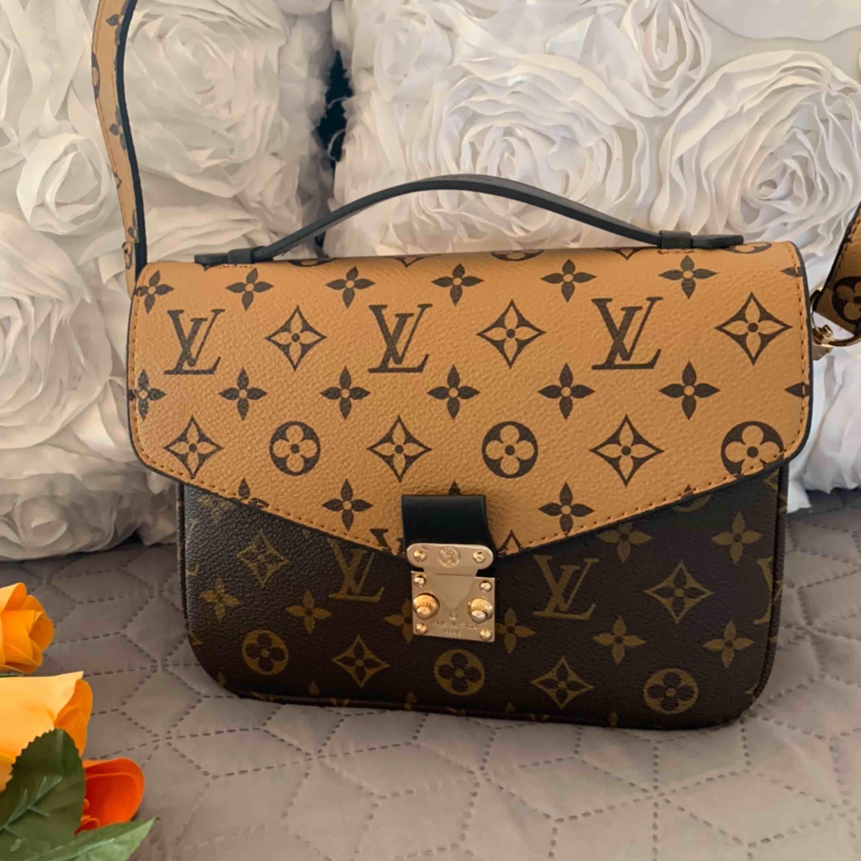 Ny väska inspirerad  Louis Vuitton Pochete metis Aa kopia Längd 24 cm, bredd 6 cm, höjd 18 cm. Oanvänd    Kan fraktas spårbar. Väskor.