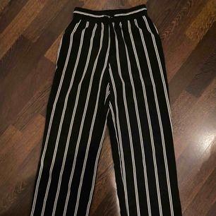 """Ett par """"kostymbyxor"""" som är svarta och vit randiga. Använt ganska mycket men dem är inte så slitna. Säljer pga för små! Tygen är stumt och lite strävt men dem är ganska luftiga."""