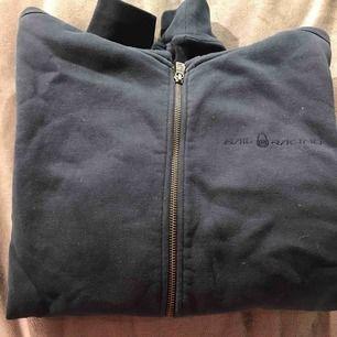 Hjälper min kille att sälja sin Sail Racing hoodie. Den är marin blå, har ett märke på vänstra ärmen och ett stort märke på ryggen. Hoodien är i bra skick och priset går att diskuteras