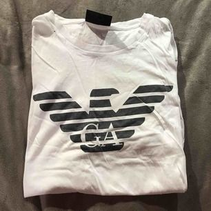 En vit Armani T-shirt med ett svart tryck på, i storlek M men passar bra på S också! Väldigt fräsch och fin!