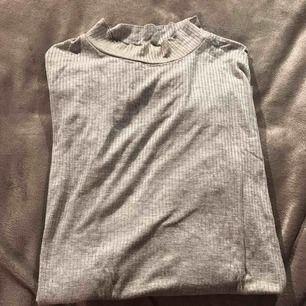 En grå långärmad tröja med polokrage, väldigt fin och bekväm!
