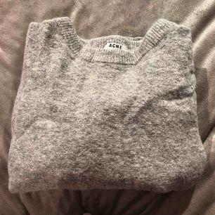 En grå stickad tröja från Acne Studios, väldigt liten i storlek och gjort på äkta ull!